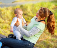 Happy young mother holding baby in hands Stock Photo