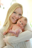 Happy Young Mother Holding Cuddly Newborn Baby Royalty Free Stock Images