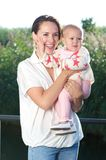 Happy young mother holding cute baby outdoors Royalty Free Stock Photos