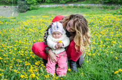 Happy young mother holding the hand of her daughter little girl baby with a bouquet of flowers of dandelions on the head that stock image