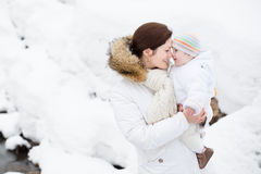 Happy young mother holding her baby in snowy park. Happy young mother holding her baby in a snowy winter park Royalty Free Stock Photo