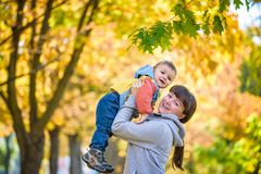 Happy young mother holding sweet toddler boy, family having fun together outside on a nice sunny autumn day. Cute adorable kid and royalty free stock photography