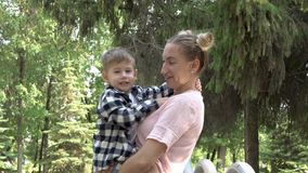 A happy young mother holds a perky, laughing baby in her arms. They hug and cuddle head to head against the background. Of green trees in the city Park. A stock footage