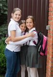 Happy young mother hugging her daughters before going to school. Portrait of happy young mother hugging her daughters before going to school Royalty Free Stock Image