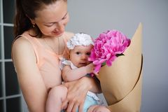 Happy young family. Mom and baby with flowers Stock Images