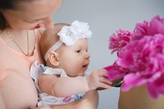 Happy young family. Mom and baby with flowers Stock Photography