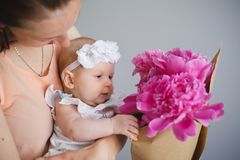 Happy young family. Mom and baby with flowers Royalty Free Stock Photo