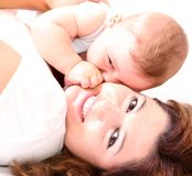 Happy young mother kissing a baby Stock Image