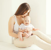 Happy young mother kissing cute baby at home Stock Photography