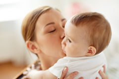 Happy young mother kissing little baby at home Royalty Free Stock Image