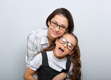 Happy young mother and lauging kid in fashion glasses hugging on empty copy space stock photos