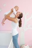 Happy young mother lifting cute baby out of crib. Portrait of a happy young mother lifting cute baby out of crib in bedroom Stock Photo