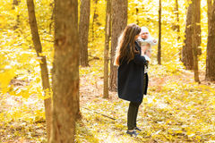 Happy young mother with little daughter in autumn Royalty Free Stock Photos