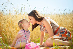 Happy young mother with little daughter on field in summer day. Happy young mother with little daughter having fun on wheat field in summer day Stock Image