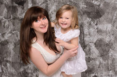 Happy young mother and little daughter. Happy young mother holding her laughing little daughter on gray wall background Royalty Free Stock Photography