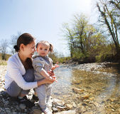 Happy young mother with little daughter near the mountain river Stock Images