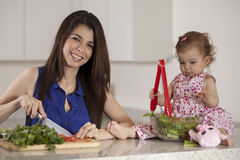 Happy young mother making dinner Royalty Free Stock Images