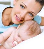 Happy young mother near sleeping newborn Stock Image
