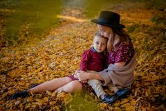 Happy young mother playing with baby in autumn park with yellow maple leaves.Family walking outdoors in autumn. Little. Boy with her mother playing in the park royalty free stock photo