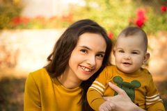 Happy young mother playing with baby in autumn park with yellow maple leaves. Family walking outdoors in autumn. Little boy with h stock photo