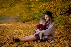 Happy young mother playing with baby in autumn park with yellow maple leaves.Family walking outdoors in autumn. Little. Boy with her mother playing in the park stock images
