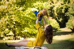 Happy young mother playing with baby in autumn park with yellow maple leaves. Family walking outdoors in autumn. Little boy with h royalty free stock images