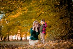 Happy young mother playing and having fun with her little baby son on sunshine warm autumn day in the park. Happy family concept