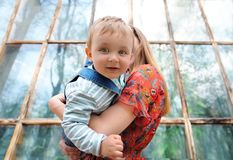 Happy young mother playing with her baby son in city park. Closeup portrait. Concept of family happiness stock photo