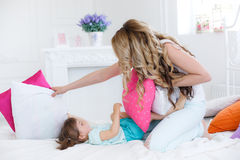 Happy young mother playing with her daughter on the bed at home Stock Photos