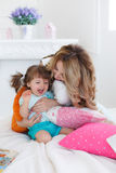 Happy young mother playing with her daughter on the bed at home Royalty Free Stock Photography
