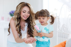 Happy young mother playing with her daughter on the bed at home Royalty Free Stock Photos