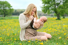 Happy Young Mother Playing with Newborn Baby Outside Stock Image