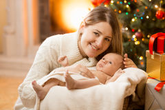Happy young mother posing with newborn baby boy at house decorat Stock Photo