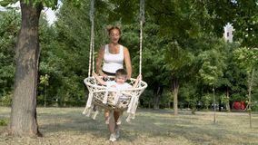 A happy young mother shakes her little son on a white swing in the Park, on a bright summer day. They laugh and play. Against the green trees. The concept of stock footage
