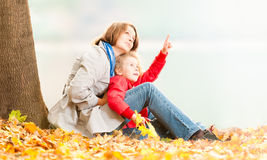 Happy young mother and small daughter. Beautiful and happy young mother together with her small daughter in the autumn park. Both sitting in maple leafs under Stock Photo