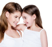 Happy young mother with a small daughter 8 years. Beautiful and happy young mother with a small daughter 8 years embrace each other at studio Stock Photos