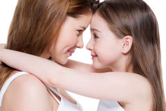 Happy young mother with a small daughter 8 years. Beautiful and happy young mother with a small daughter 8 years embrace each other at studio Royalty Free Stock Photos