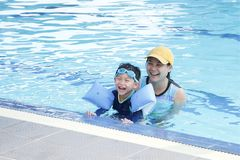 Happy young mother and son having fun together in pool royalty free stock image