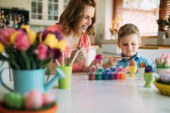 Happy young mother and son are painting Easter eggs. Happy young mother and son are sitting at a table painting Easter egg royalty free stock photo