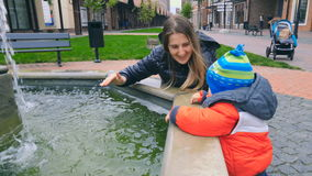 Happy young mother splashing with her baby son at fountain on street stock video footage