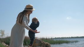 Happy young mother in straw hat with toddler boy throw small pebbles into water while resting on river and enjoy. Outdoor recreation stock video footage