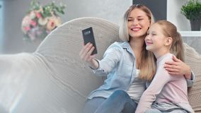 Happy young mother and teen daughter posing taking selfie using smartphone relaxing at home stock video