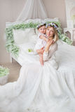 Happy young mother with to her little baby in a bedroom Royalty Free Stock Photos