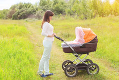 Happy young mother walking with baby stroller outdoors Stock Photo