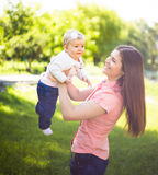 Happy young mother walking with her cute baby at summer sunny day. Happy young mother spend time with her cute baby at summer sunny day royalty free stock images
