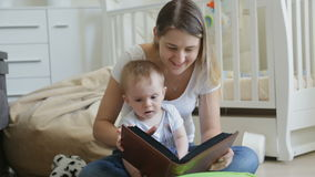 Happy young mother watching family photo album with her baby son on floor at living room