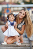Happy young mother with a young daughter near Yacht Club Royalty Free Stock Photography