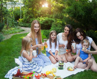 Happy young mothers and daughters having picnic in summer park Royalty Free Stock Image