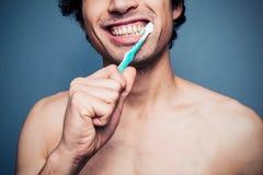 Happy young multi racial man brushing his teeth Stock Photos