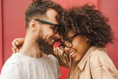 Happy young multicultural couple in eyeglasses hugging. On street royalty free stock photos